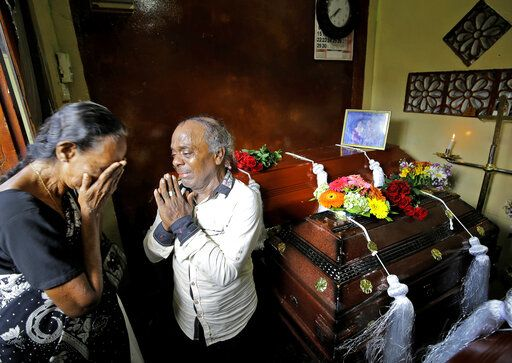 A Sri Lankan family mourns next to the coffins of their three family member, all victims of Easter Sunday bombing, in Colombo, Sri Lanka, Tuesday, April 23, 2019. The six near-simultaneous attacks on three churches and three luxury hotels and three related blasts later Sunday were the South Asian island nation's deadliest violence in a decade while Sri Lanka police arrested 40 suspects in the wake of a state of emergency that took effect Tuesday giving the military war-time powers.