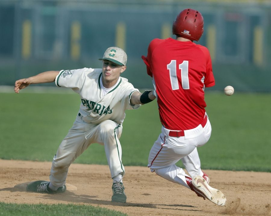 Mundelein's Justin Binzn (11) is safe at second as Stevenson's Chris Farina reaches for the ball during their game Tuesday at Stevenson High School in Lincolnshire.