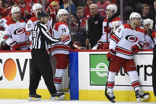Carolina Hurricanes left wing Micheal Ferland (79) is shown to the bench by linesman Kiel Murchison (79) after he received a match penalty for a hit to the head of Washington Capitals' Nic Dowd, not seen, during the second period of Game 2 of an NHL hockey first-round playoff series, Saturday, April 13, 2019, in Washington. The Capitals won 4-3 in overtime. (AP Photo/Nick Wass)