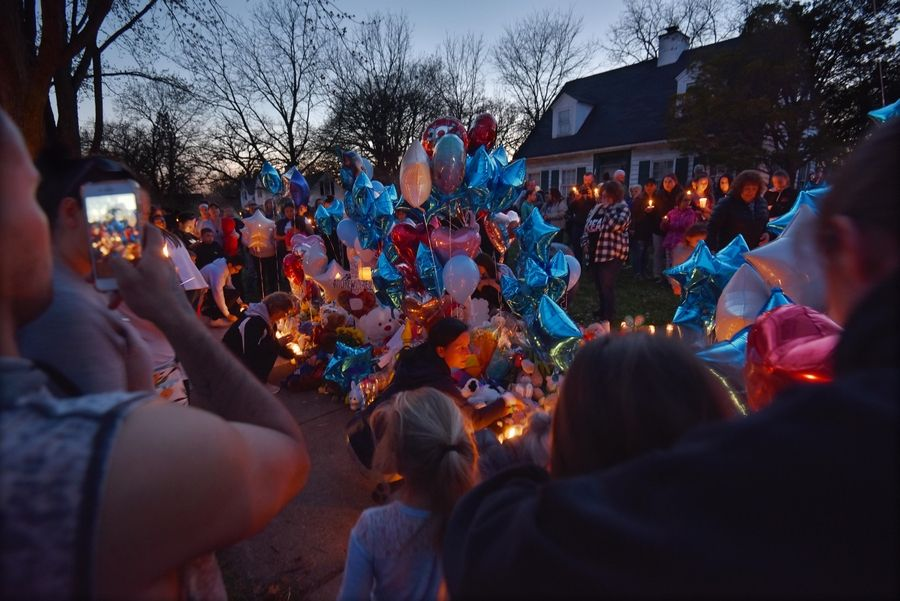 "People linger Wednesday night around a memorial on the lawn of the Freund home in Crystal Lake. The body of 5-year-old Andrew ""AJ"" Freund had been found earlier in the day near Woodstock, and his parents have been charged with his murder."