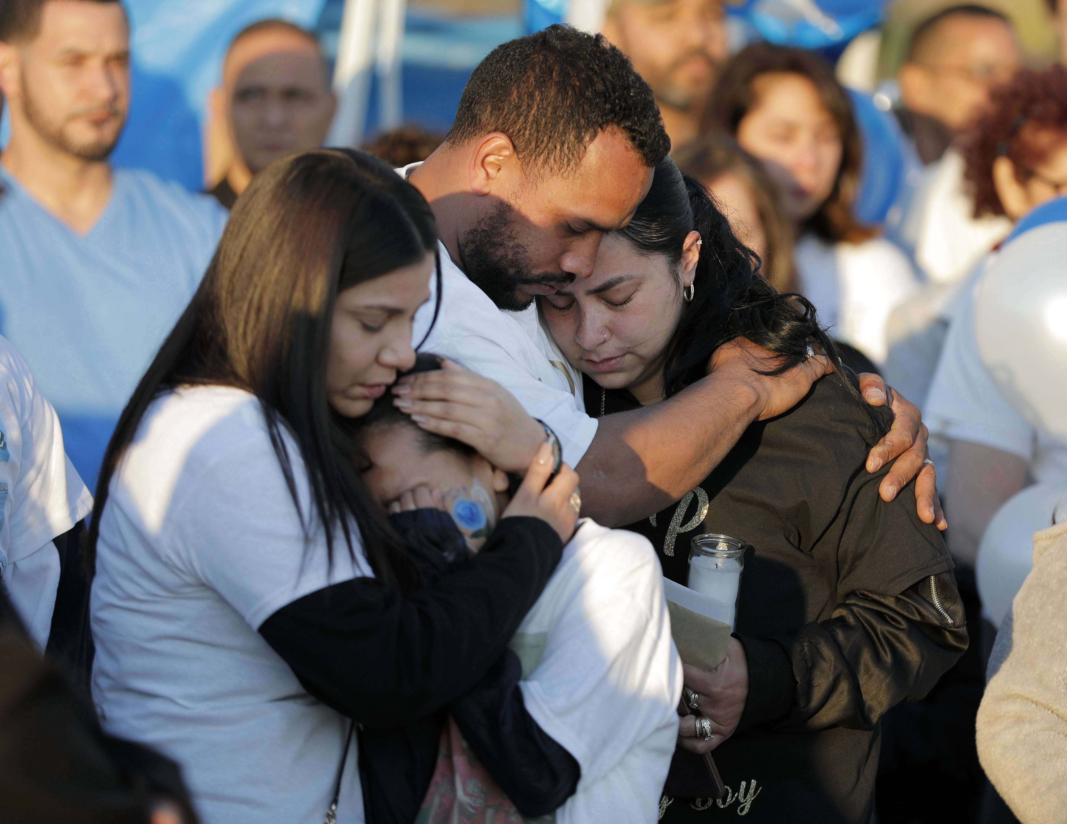 Family members embrace during a public memorial Wednesday for 9-year-old Geraldo Rodriguez, who died after falling off a paddleboat into the water last Friday at Lake View Villa Beach in Wauconda. Geraldo would have turned 10 on Wednesday.