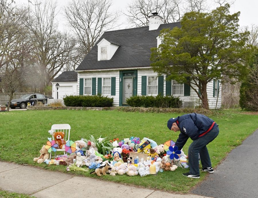 "A man places a candle on a growing memorial outside the Crystal Lake home of 5-year-old Andrew ""AJ"" Freund on Wednesday after the announcement that the boy's parents have been charged with his murder."