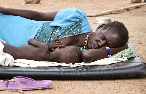In this photo taken Wednesday, April 17, 2019, Agiu Nyang, 1, who is sick with measles, is nursed by his mother Amel Makir as she lies on the ground at the hospital in Kuajok, South Sudan. As South Sudan emerges from a five-year civil war it is grappling with a measles outbreak in which more than 750 cases, including seven deaths, have been reported since January - almost six times the number of cases for all of 2018, according to WHO data.