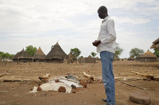 In this photo taken Wednesday, April 17, 2019, John Garang Ajak stands in his yard looking at the grave of his nephew who died in March after contracting measles, in Kuajok, South Sudan. As South Sudan emerges from a five-year civil war it is grappling with a measles outbreak in which more than 750 cases, including seven deaths, have been reported since January - almost six times the number of cases for all of 2018, according to WHO data.