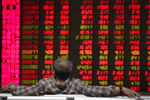 A man looks at an electronic board displaying stock prices at a brokerage house in Beijing, Wednesday, April 24, 2019. Shares were mostly lower in Asia on Wednesday despite the S&P 500's all-time record high close the day before. (AP Photo/Andy Wong)