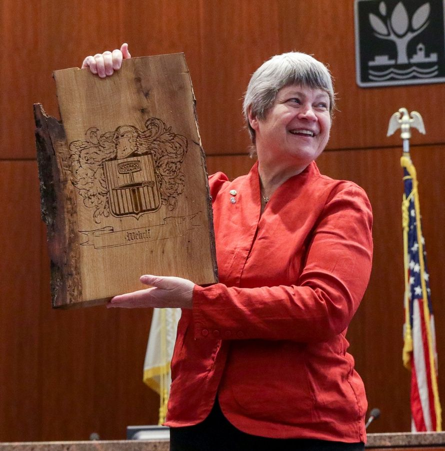 "DuPage County Forest Preserve Commissioner Mary Lou Wehrli holds a piece of Hobson wood inscribed with her family crest. The gift from Naperville Unit District 203 architecture and pre-engineering students served as a ""thank you"" for helping them with their projects to develop a vision for the Greene Farm barn."