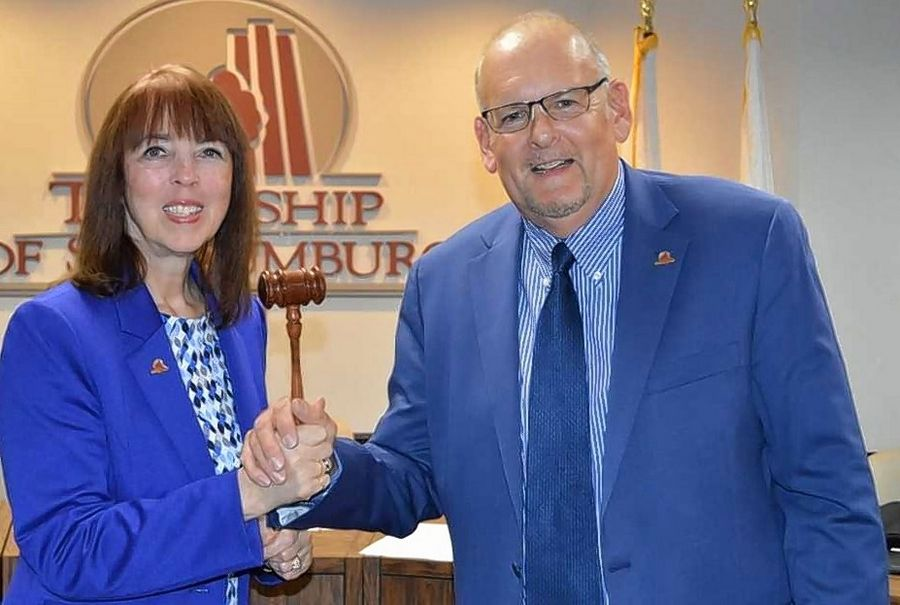 Retiring after 18 years as Schaumburg Township supervisor Wednesday, Mary Wroblewski ceremonially passes her gavel to her board-appointed successor, longtime township Clerk Timothy Heneghan.