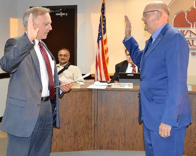 Former Schaumburg Township Clerk Timothy Heneghan, right, takes the oath of office as township supervisor from attorney Gary Seyring Wednesday to succeed the retired Mary Wroblewski.