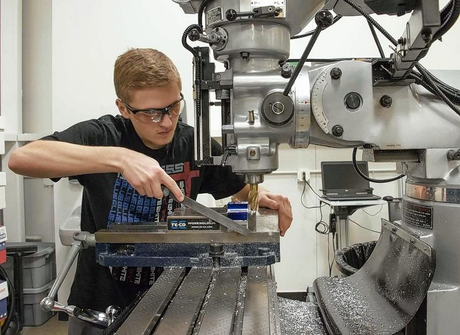 McHenry County College CNC apprentice James Friend of Cary deburrs a metal part on the mill during his Introduction to Manual Machining class. He is one of eight students who joined MCC's new Apprenticeship Program for advanced manufacturing to receive on-the-job training and education toward an Associate in Applied Science degree in engineering technology.