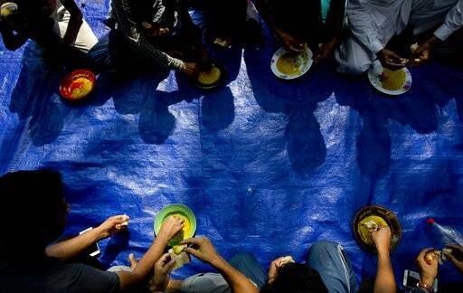 Ahmadi Muslim refugees eat a meal at a community center that they took refuge in Pasyala, north east of Colombo, Sri Lanka, Thursday, April 25, 2019. Hundreds of Ahmadi Muslims from Pakistan who sought refuge in Sri Lanka now huddle together in fear following attacks and harassment after the Easter bombings. They are just some of the Muslims scared the Islamic State-claimed assault will bring both government and mob retaliation. (AP Photo/Gemunu Amarasinghe)
