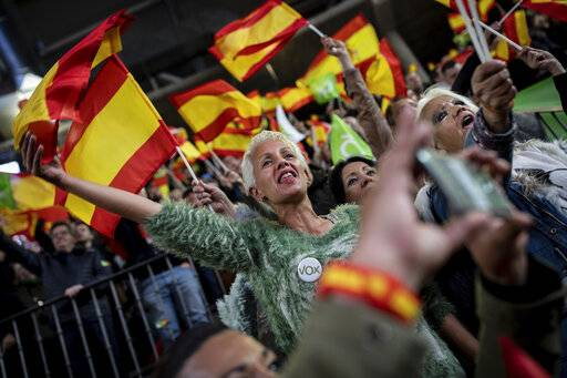 In this Saturday, April 6, 2019 photo, supporters of Spain's far-right Vox Party wave Spanish and VOX flags during a party event in Leganes, on the outskirts of Madrid, Spain. A substantial pool of undecided voters and a right-wing splintered by a rising populist party are making confident predictions harder to come by as Spain prepares for its third parliamentary election in less than four years. (AP Photo/Bernat Armangue)