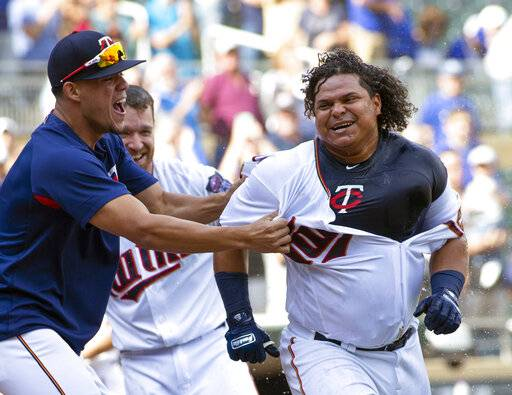 "FILE - In this Sept. 9, 2018, file photo, Minnesota Twins' Willians Astudillo, right, is mobbed by teammate Jose Berrios after hitting a 2-run home run during the ninth inning of a baseball game against the Kansas City Royals, in Minneapolis. The most popular player on the first-place Minnesota Twins is the third-string catcher and versatile everyman Willians Astudillo, whose all-out style has endeared him to the team and the fans since his debut last season. His cult hero status reaches a new high on Friday night, when the Twins give away ""La Tortuga� T-shirts in honor of his nickname, which means turtle in Spanish, at their game against Baltimore."