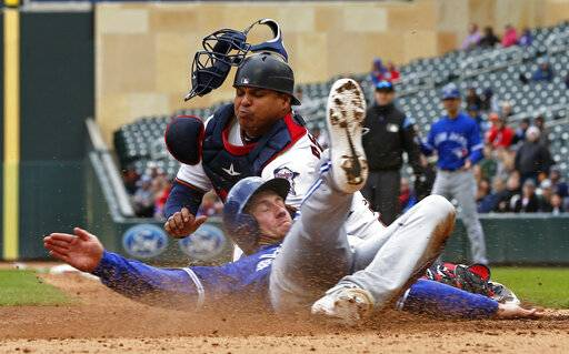 Toronto Blue Jays' Billy McKinney, right, beats the tag by Minnesota Twins catcher Willians Astudillo to score on a three-run, bases loaded double by Eric Sogard off Twins pitcher Michael Pineda in the fourth inning of a baseball game Thursday, April 18, 2019, in Minneapolis.