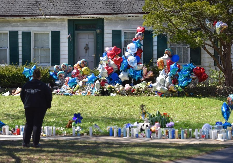 "Mourners stop at the home of Andrew ""AJ"" Freund Friday on Dole Avenue in Crystal Lake as a memorial of balloons, stuffed animals, flowers, toys and candles grows."