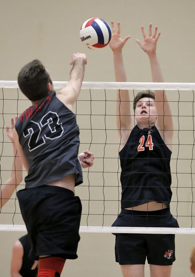 Palatine's Michael Green, left, and Libertyville's Ben Moss meet at the net during their game Saturday at Libertyville High School.