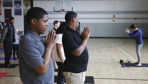 Students including Tylan Leggans, front, perform the mountain pose during the life skills yoga mindfulness class at Eisenhower High School in Decatur, Ill.  (Jim Bowling/Herald & Review via AP)