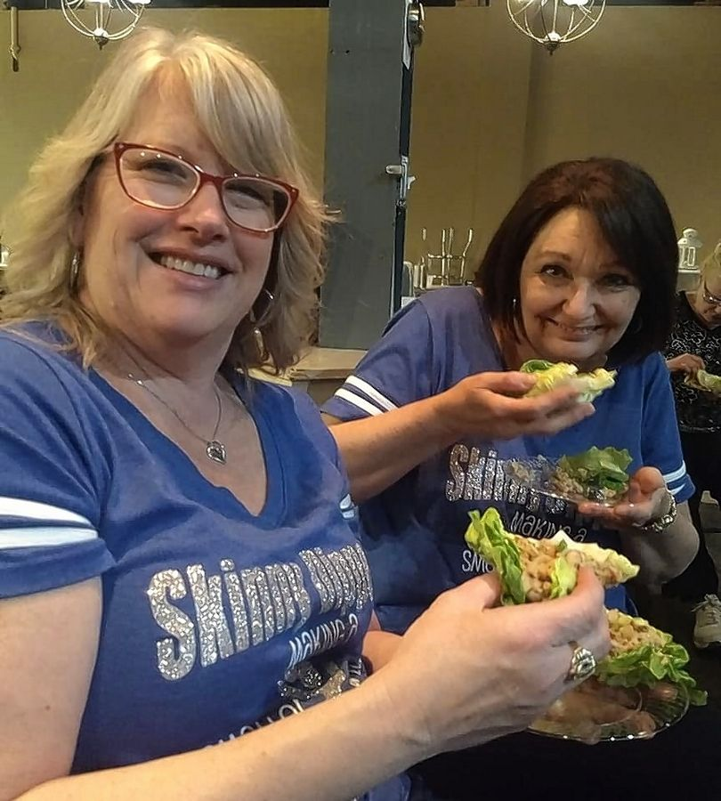 "Lori Tobler and Barb Merner of Fitz Chem LLC's ""Skinny Dippers"" enjoy some healthy lettuce wraps created by Chef Miguel at Cooking Skills Academy."