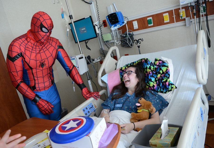 Gianna Greco, 17, of Streamwood is all smiles as she gets a visit from Spider-Man in her hospital room Sunday at Amita Health Women & Children's Hospital in Hoffman Estates. Spider-Man is Ray Wisbrock of Palatine. He volunteers as a superhero for the Holiday Heroes program at area hospitals.