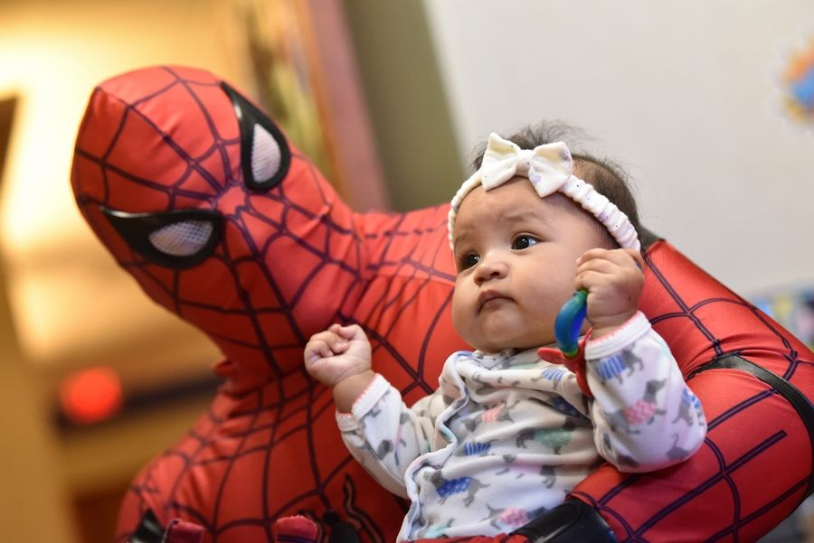 Sabrina Hernandez, 6 months, of Brookfield gets an up close visit with Spider-Man on Sunday at Amita Health Women & Children's Hospital in Hoffman Estates. Spider-Man is Ray Wisbrock of Palatine.