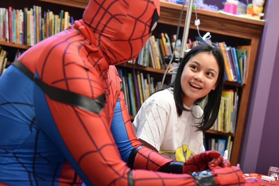Danica Arenas, 11 of Hanover Park, talks with Spider-Man at Amita Health Women & Children's Hospital in Hoffman Estates on Sunday. Spider-Man is Ray Wisbrock of Palatine, who volunteers to visit kids in hospitals through the Holiday Heroes program.