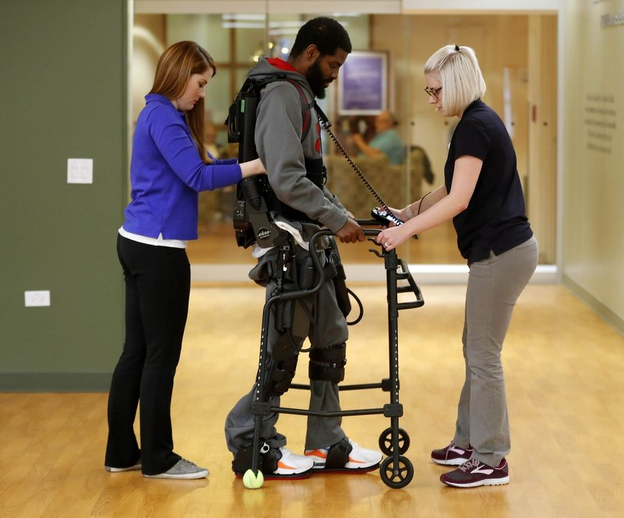Lauren Bularzik, left, and tech Erica Pickering help Christopher Burks of Maywood use a robotic exoskeleton as part of his therapy at Marianjoy Rehabilitation Hospital in Wheaton.