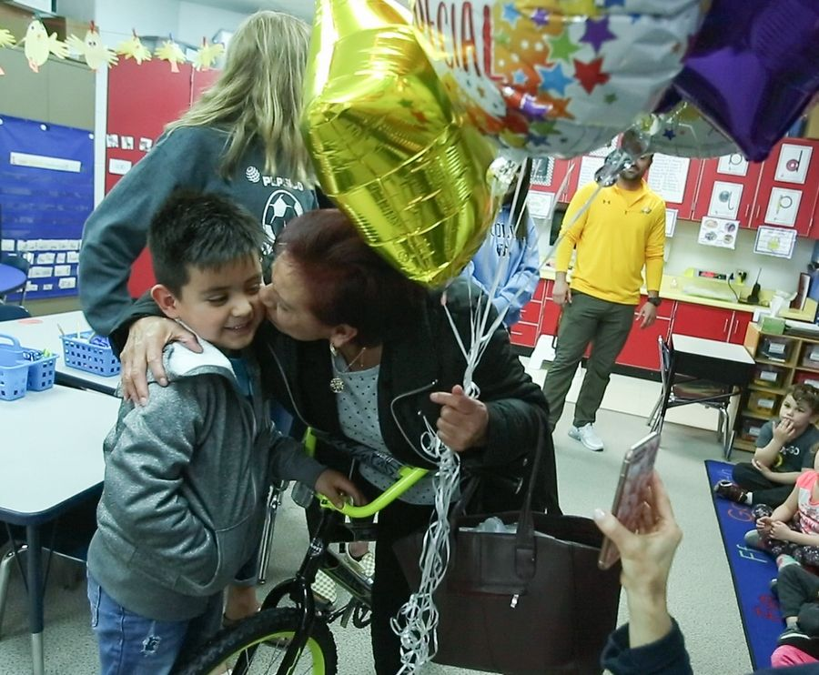 Ian Alexander Morales Nava, a kindergartner at Eastview Elementary in Algonquin, gets a kiss and balloons from his grandmother Dominga Flores after he was surprised Tuesday with new bicycle built by members of the Jacobs High School girls soccer team. He is among 100 kids in kindergarten to second grade in the region who are receiving new bikes during Month of the Military Child.