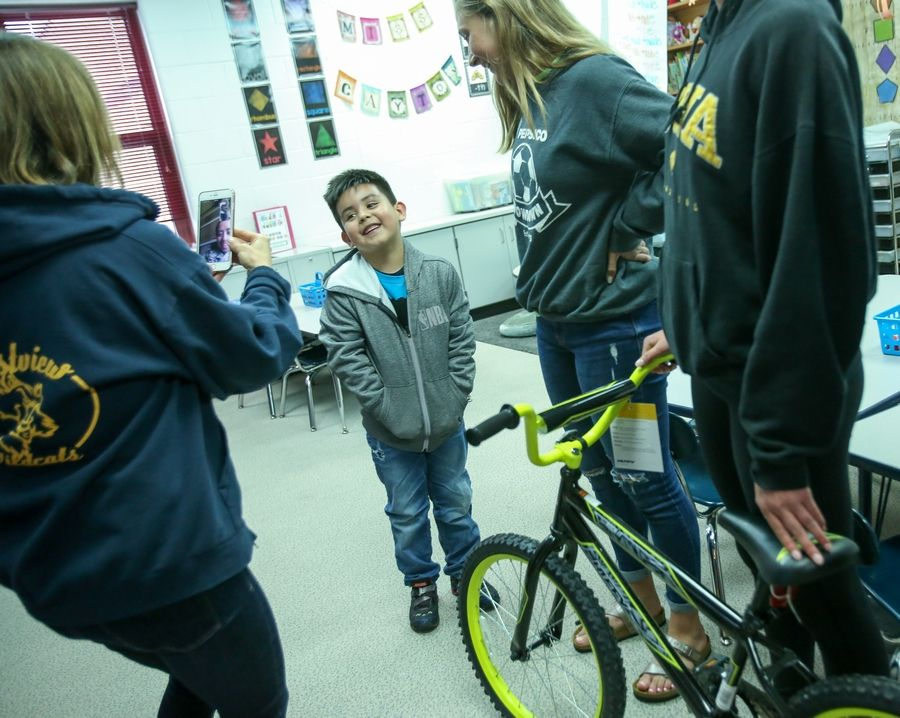 Ian Alexander Morales Nava, a kindergartner at Eastview Elementary in Algonquin, was surprised Tuesday with a new bicycle assembled by members of the Jacobs High School girls soccer team, including senior Cassie Kowalski, right. Ian's mother, Claudia Nava, looked on through FaceTime. She is in training in Virginia with the Illinois National Guard.