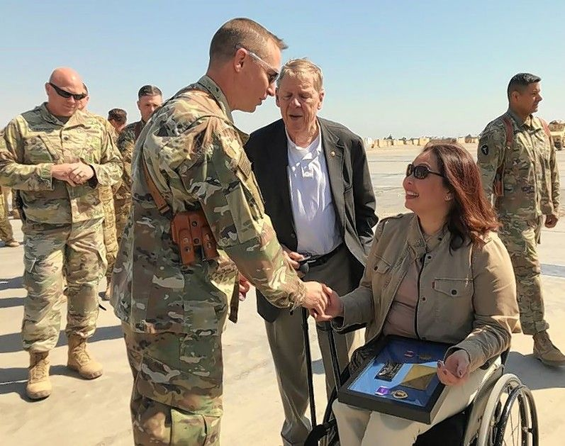 Democratic U.S. Sen. Tammy Duckworth meets with U.S. troops in Iraq last week, 15 years after the Blackhawk helicopter she was piloting there was shot down by enemy fire.