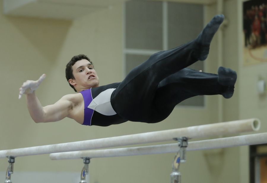 Downers Grove North's Jonah Kopecky competes on the parallel bars during boys sectional gymnastics Wednesday at Libertyville High School.