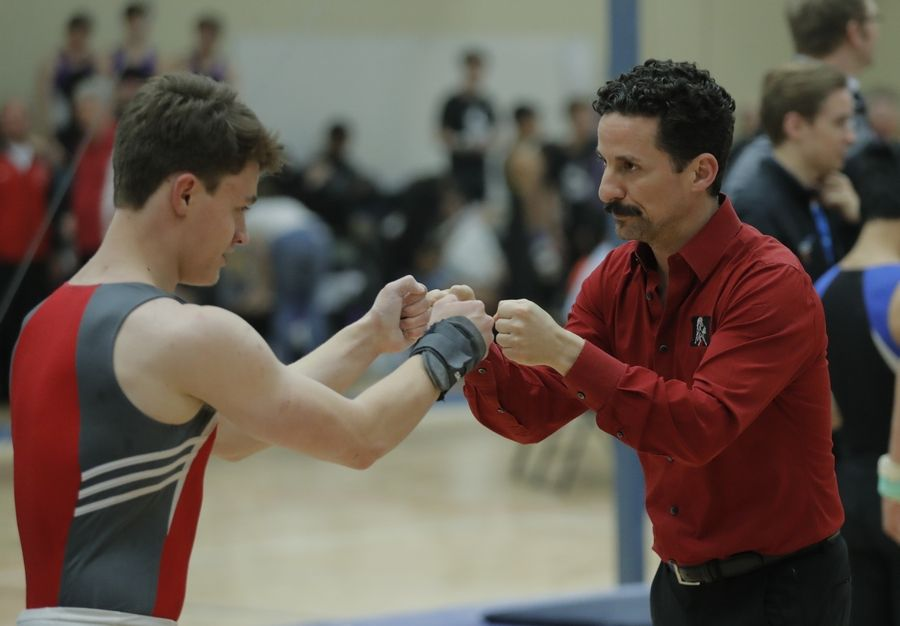 Mundelein's Will Fero is congratulated by coach Jesse Piland after competing on the pommel horse during boys sectional gymnastics Wednesday at Libertyville High School.