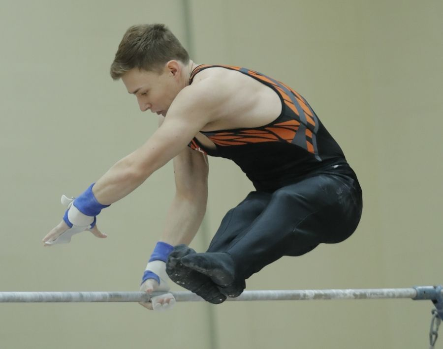 Libertyville's Max Faber does a release move on the high bar during boys sectional gymnastics Wednesday at Libertyville High School.