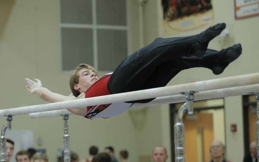 Barrington's Braedon Wever competes on the parallel bars during boys sectional gymnastics Wednesday at Libertyville High School.