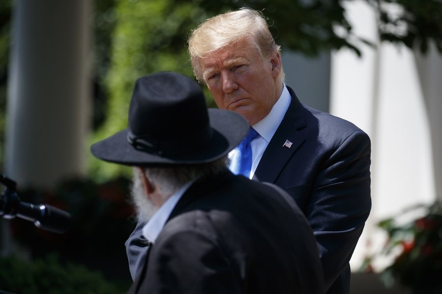 President Donald Trump looks on Thursday as Rabbi Yisroel Goldstein, survivor of the Poway, Calif synagogue shooting, speaks during a National Day of Prayer event in the Rose Garden of the White House.