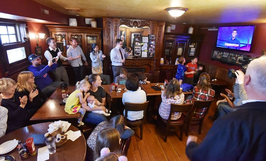 "Ian Holzhauer, in sweater vest in the left rear corner, claps at a watch party for his brother, Naperville native James Holzhauer, who is breaking records on ""Jeopardy!"" at Quigley's Irish Pub in downtown Naperville."