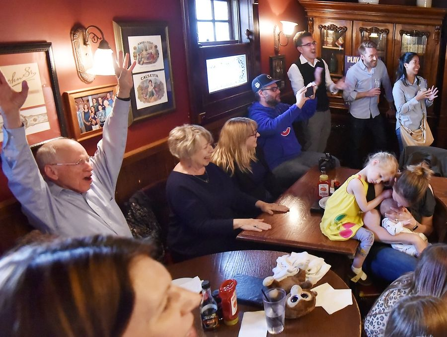 "As Naperville native James Holzhauer wins on ""Jeopardy!"" at Quigley's Irish Pub in downtown Naperville Friday, his father Juergen, left with hands up, and brother Ian, in sweater vest left rear corner, celebrate with a room full of family and friends."