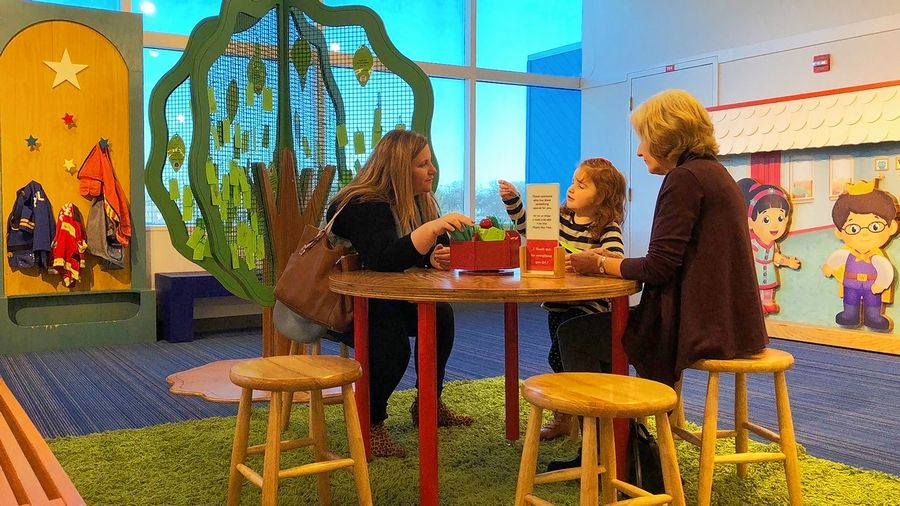 Museum visitors write thank-you notes to hang on the Thank You Tree in Daniel Tiger's Neighborhood: A Grr-ific Exhibit at the DuPage Children's Museum