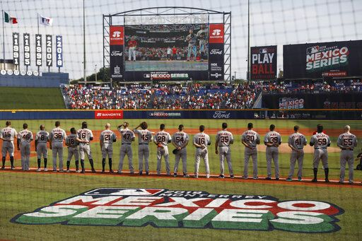The Houston Astros stand during the playing of national anthems at the start of a baseball game against the Los Angeles Angels, in Monterrey, Mexico, Saturday, May 4, 2019.