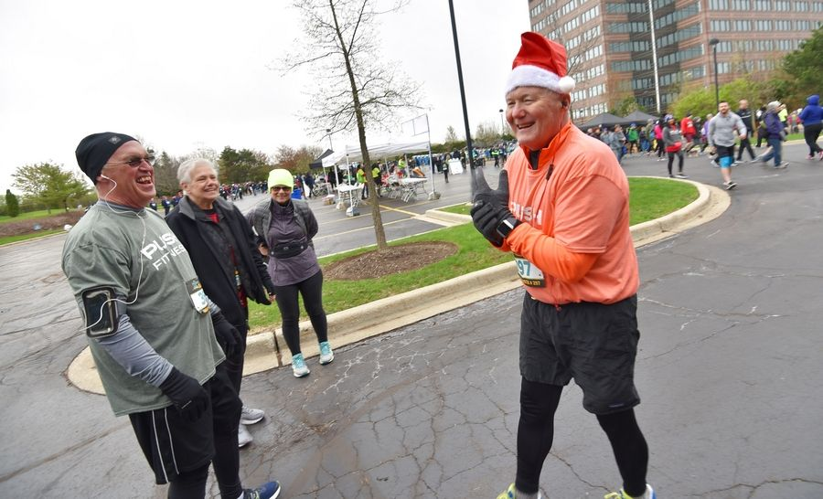 Contestant Ed Poczatek wears a Santa hat and laughs with other contestants before the snow started at the Human Race 5K.