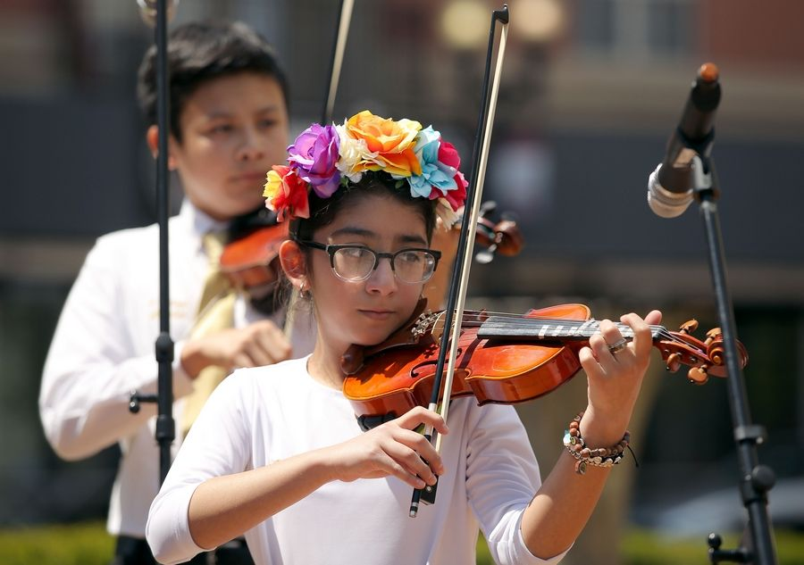 Bella Olivios, right, 11, and Alex Koppari, 14, of the musical group 4 Strings Attached of McHenry play traditional Mexican music Sunday as the Downtown Neighborhood Association of Elgin hosted a Cinco De Mayo celebration.