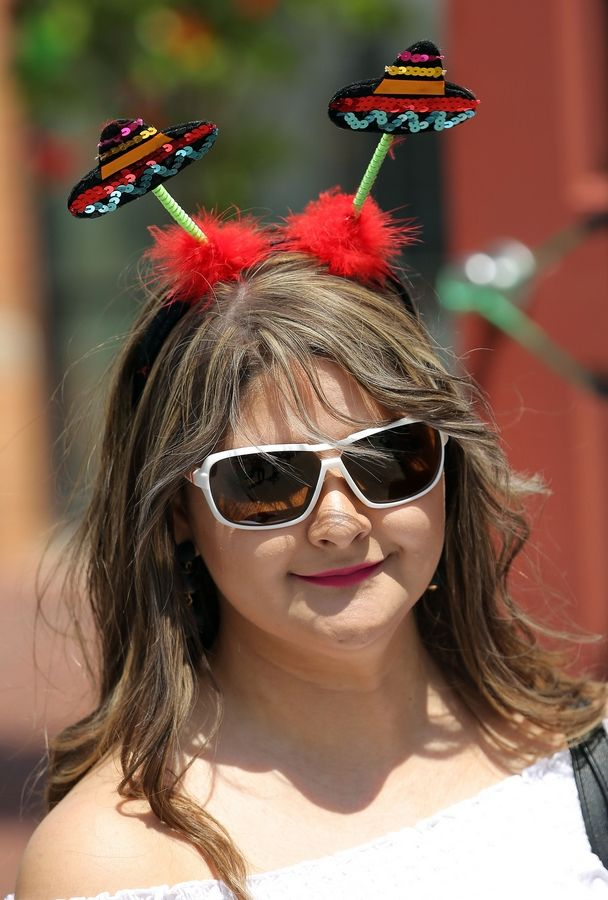Vianey Tello of Carpentersville wears Mexican sombrero antennas during a Cinco De Mayo celebration Sunday hosted by the Downtown Neighborhood Association of Elgin.