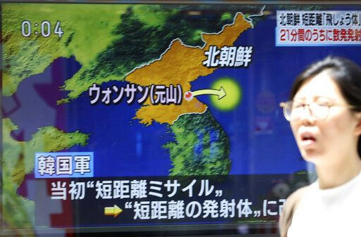 People walk past a screen showing a TV news on unidentified short-range projectiles fired by North Korea, in Tokyo, Saturday, May 4, 2019. North Korea on Saturday fired several unidentified short-range projectiles into the sea off its eastern coast, the South Korean Joint Chiefs of Staff said, a likely sign of Pyongyang's growing frustration at stalled diplomatic talks with Washington meant to provide coveted sanctions relief in return for nuclear disarmament.