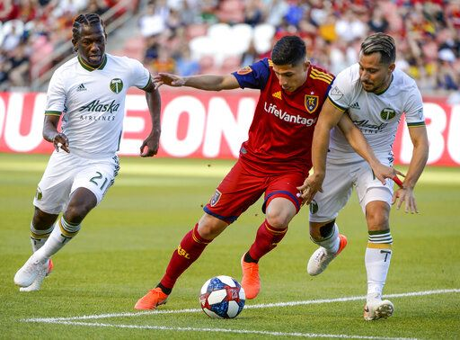 Portland Timbers midfielders Diego Chara (21) and Sebastian Blanco (10) pressure Real Salt Lake forward Jefferson Savarino during an MLS soccer match Saturday, May 4, 2019, in Sandy, Utah. (Leah Hogsten/The Salt Lake Tribune via AP)