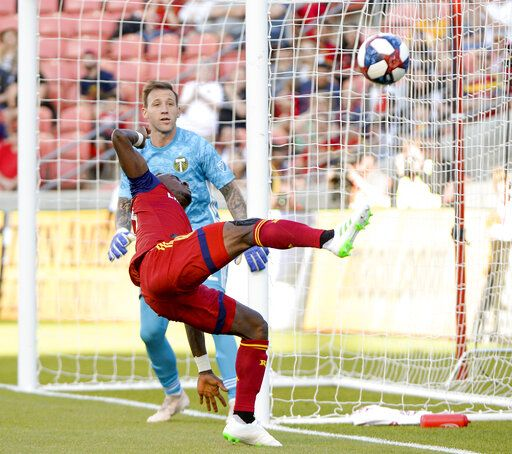 Real Salt Lake forward Sam Johnson, front, misses a foot on the ball in front of Portland Timbers goalkeeper Steve Clark, top, during an MLS soccer match Saturday, May 4, 2019, at Rio Tinto Stadium in Sandy, Utah. (Leah Hogsten/The Salt Lake Tribune via AP)