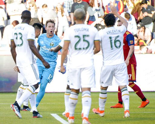 Portland Timbers goalkeeper Steve Clark (12) celebrates after saving a penalty kick off Real Salt Lake midfielder Albert Rusnak (11) in the first half of an MLS soccer match Saturday, May 4, 2019, at Rio Tinto Stadium in Sandy, Utah. (Leah Hogsten/The Salt Lake Tribune via AP)