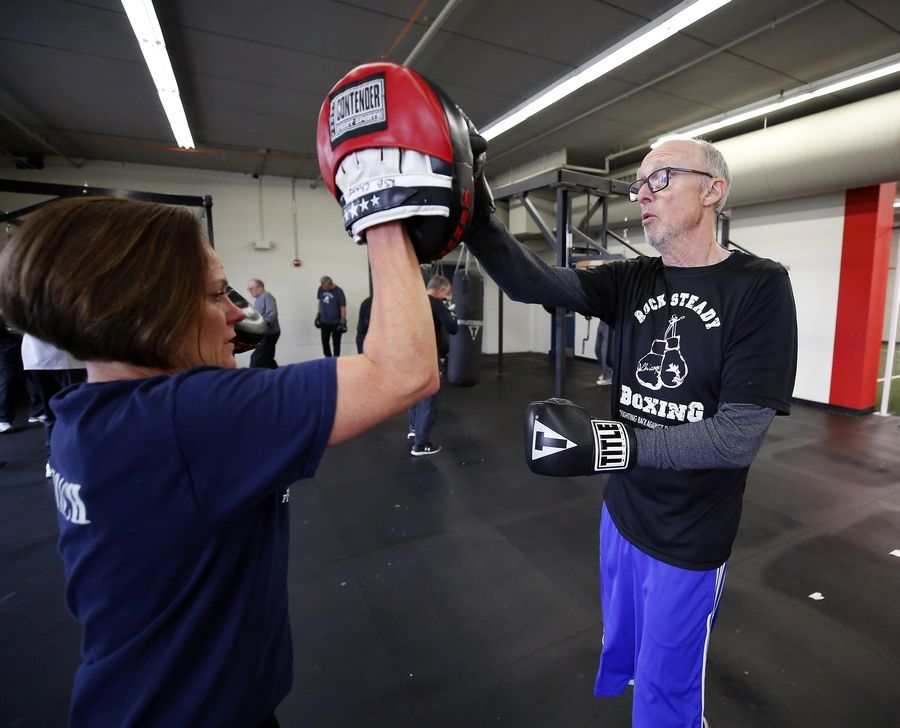 Dennis O'Malley of St. Charles works on mitt drills with coach Judi Andersen during a Rock Steady Boxing class for people with Parkinson's disease.