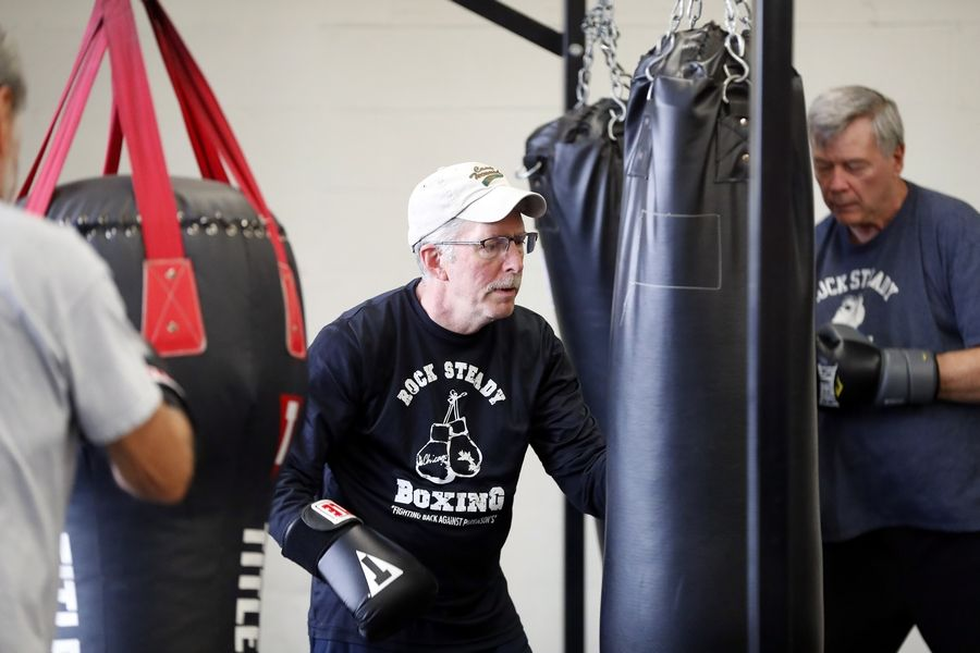 Jim McCullough of St. Charles, center, hits a heavy bag during a Rock Steady Boxing class at the Eastside Recreation Center in Elgin.