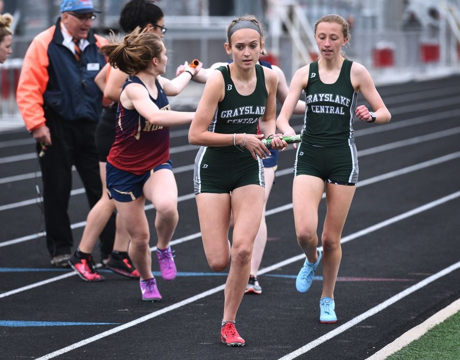 Grayslake Central's Grace Kokkin, right, hands the baton to teammate Lauren Brunk during the 4 x 800 relay at Thursday's girls track sectional in Antioch.