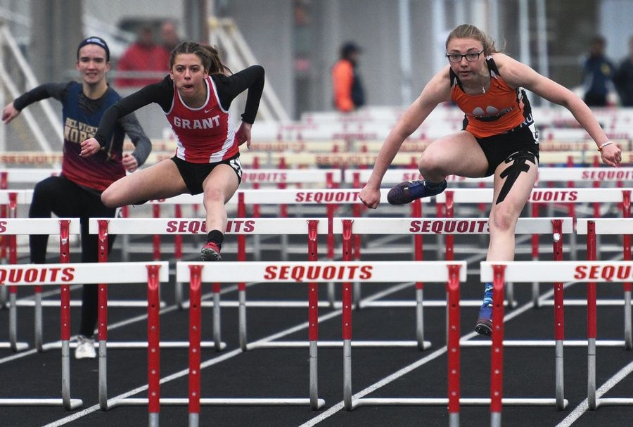 Grant's Drue Polka, left, goes head-to-head with Harlem's Cloey Fare in the 100-meter hurdles during Thursday's girls track sectional in Antioch.
