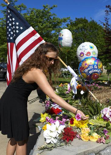 Brittney Jones, a family friend of Riley Howell, places flowers outside the Stuart Auditorium where his memorial service was held in Lake Junaluska, N.C., Sunday, May 5, 2019. Family, hundreds of friends and a military honor guard on Sunday remembered Howell, a North Carolina college student credited with saving classmates by rushing a gunman firing inside their lecture hall.