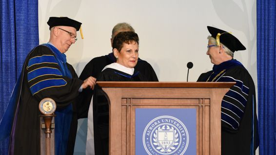 Frank Buscher, vice president for academic affairs, left, assists Tom Cross, director of the Institute for Collaboration, and President Rebecca L. Sherrick, right, in recognizing Rita B. Garman as the recipient of the degree of Doctor of Humane Letters during the spring graduate commencement ceremony.